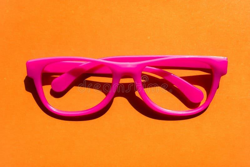 Occhiali rosa di plastica isolati su fondo arancio Concetto divertente dei pantaloni a vita bassa fotografia stock