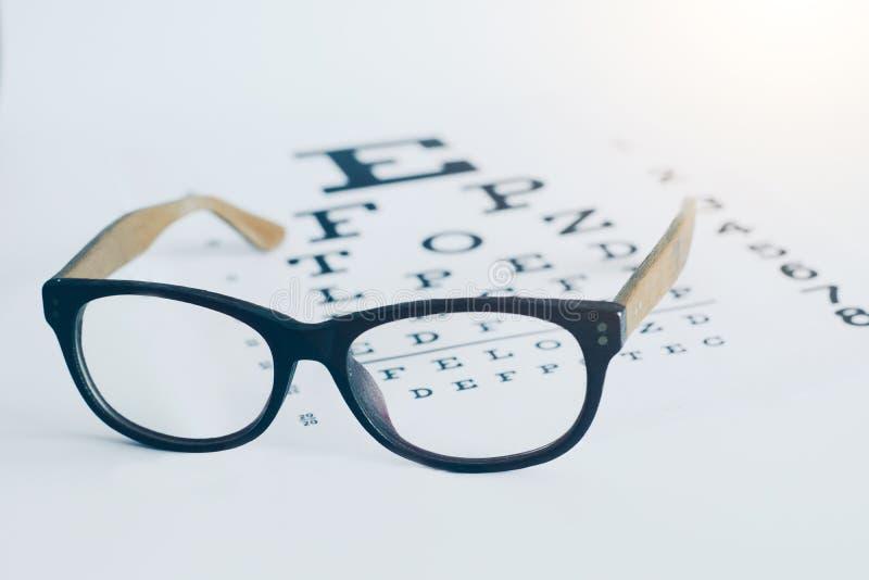Occhiali su un grafico visivo del testo dell'ottico con fondo bianco Concetto dell'ottico di vista fotografia stock