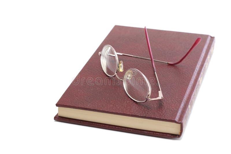 Occhiali su un libro fotografie stock
