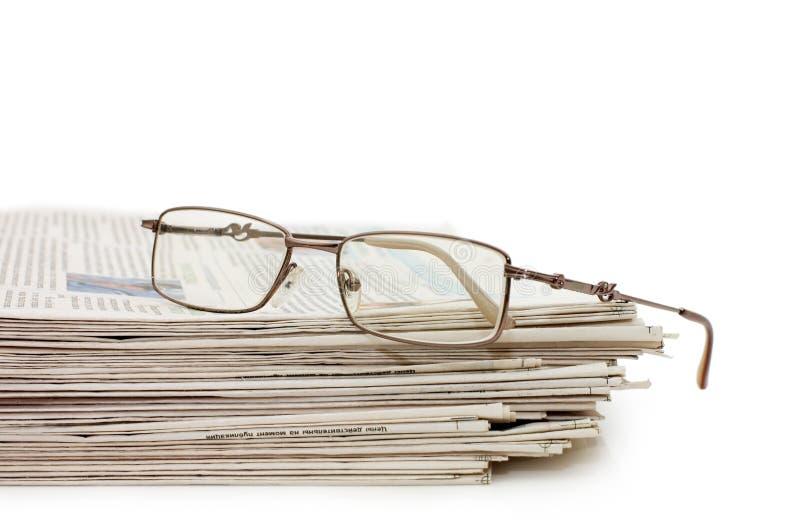 Occhiali su un mucchio dei giornali fotografie stock libere da diritti