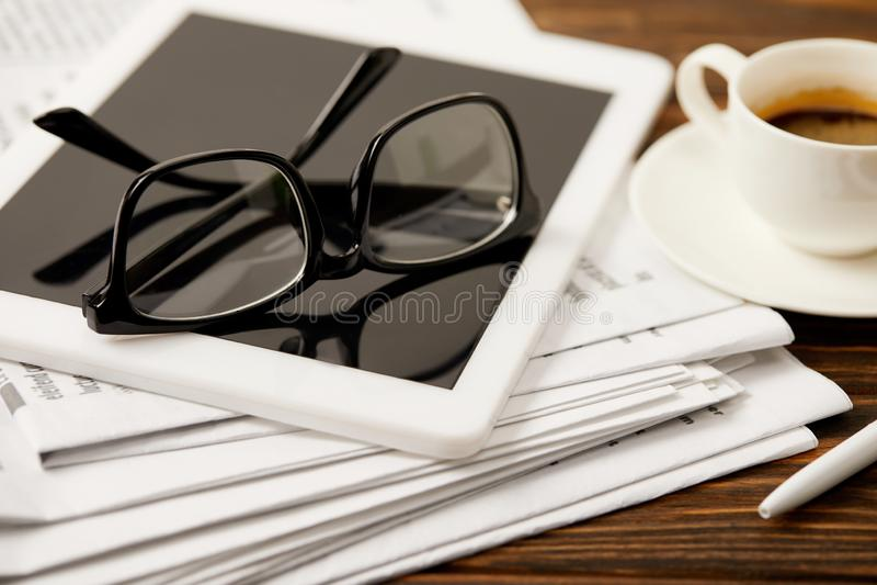 occhiali, tazza di caffè, compressa digitale e giornali sulla tavola di legno fotografie stock