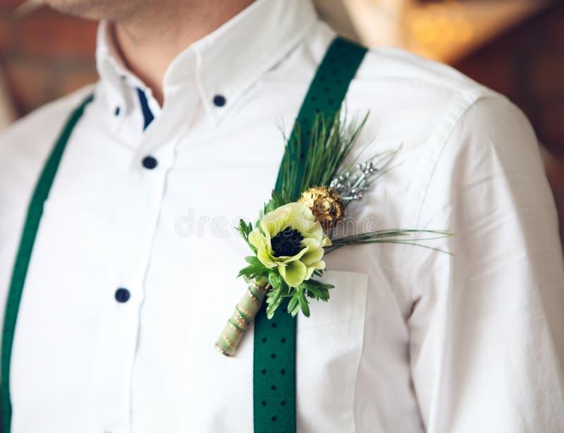 Occhiello d'uso dello sposo con l'anemone bianco immagine stock