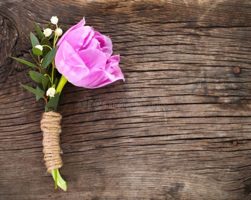 Occhiello porpora del tulipano per lo sposo sui precedenti di legno fotografia stock