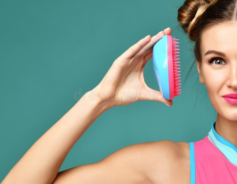 Occhio castana di fine della donna di modo felice con la spazzola popolare blu rosa variopinta del pettine dei capelli fotografie stock libere da diritti