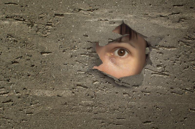 Occhio che guarda attraverso un foro in parete. fotografia stock libera da diritti