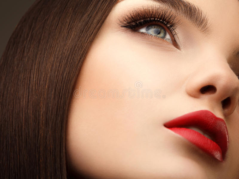 Occhio della donna con bello trucco ed i cigli lunghi. Labbra rosse. Ciao fotografia stock libera da diritti