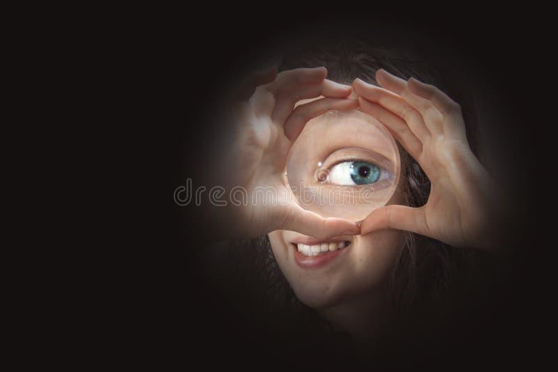 Occhio femminile che guarda con la fine della lente d'ingrandimento su fotografie stock libere da diritti
