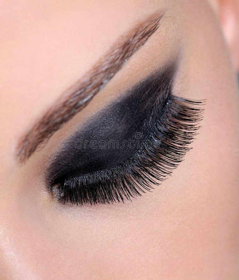 Occhio femminile con trucco luminoso di fascino immagini stock