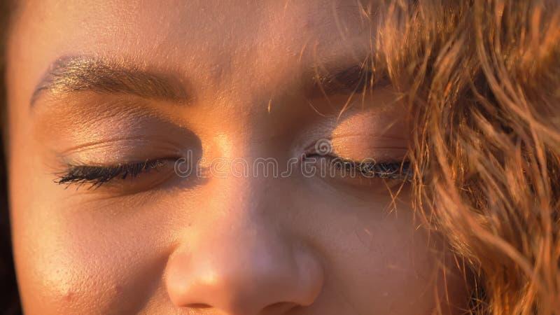 Occhio-ritratto del primo piano della ragazza caucasica abbastanza riccio-dai capelli con gli occhi chiusi immagini stock