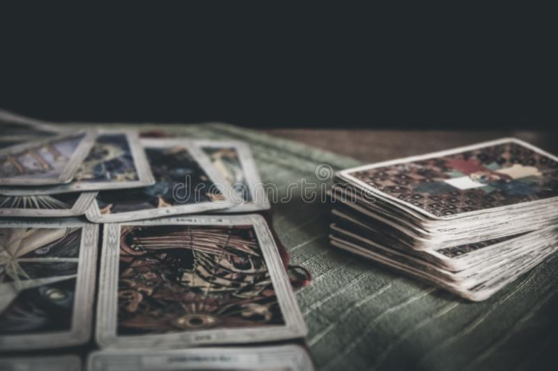 Occult mystic tarot deck and old tarot cards laying on table for a magical pagan ritual psychic destiny reading royalty free stock image