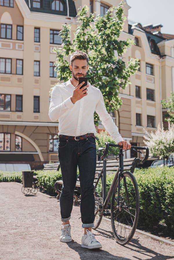 occupé obtenez Jeune position châtain d'homme en parc avec une bicyclette et regarder son téléphone images libres de droits