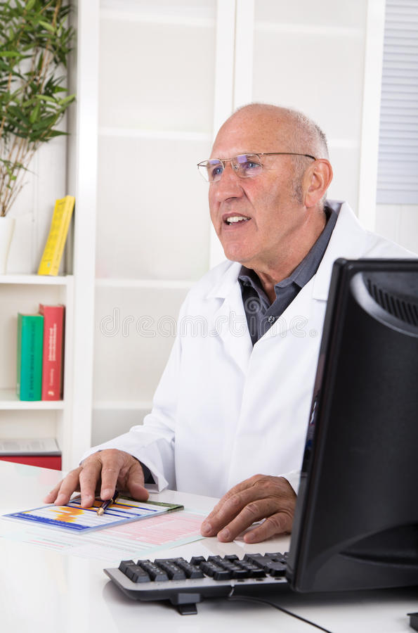 Occupation: portrait of an older male doctor. Sitting in the office royalty free stock images