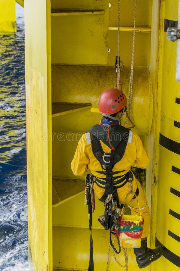Occupation. Working at height. A commercial abseiler hanging with fall arrestor device doing painting activity on oil and gas platform jacket royalty free stock photos