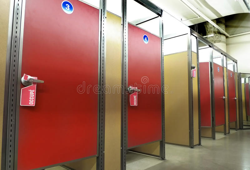 Occupied dressing rooms. Dressing rooms in a row with open and closed doors with occupied signs royalty free stock image