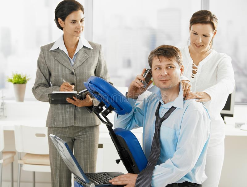 Occupied executive getting massage stock photo