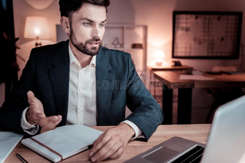 Occupied responsible worker looking at the laptop and communicating. royalty free stock photo