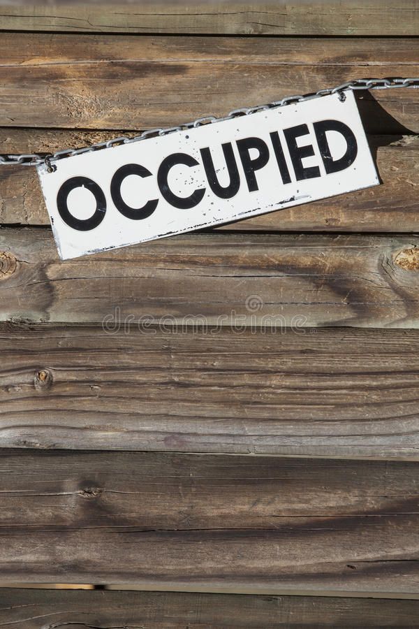 Occupied. White metal sign with the word occupied hanging at a chain in front of a wooden wall. Concept for all things being occupied stock photography