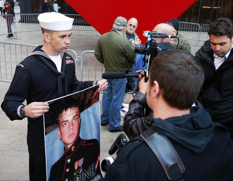 Occupy Wall Street Protest. In Zuccotti Par, at the Occupy Wall Street Protest, aUS Navy seaman displays poster of Scott Olsen, an Iraq War veteran who suffered royalty free stock photography