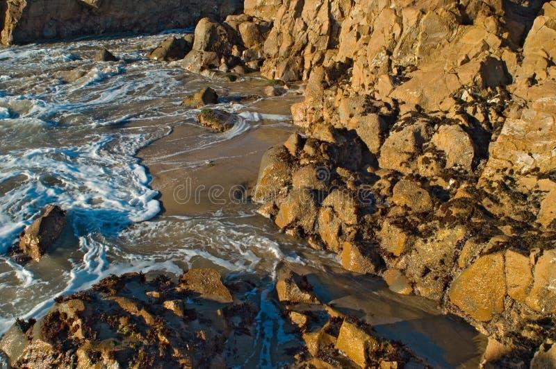 Oceaan branding bij zonsondergang stock afbeelding