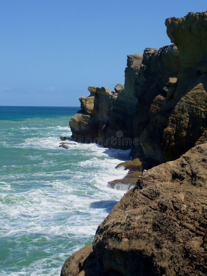 Oceaan die op kustrotsgezicht schommelen stock afbeeldingen