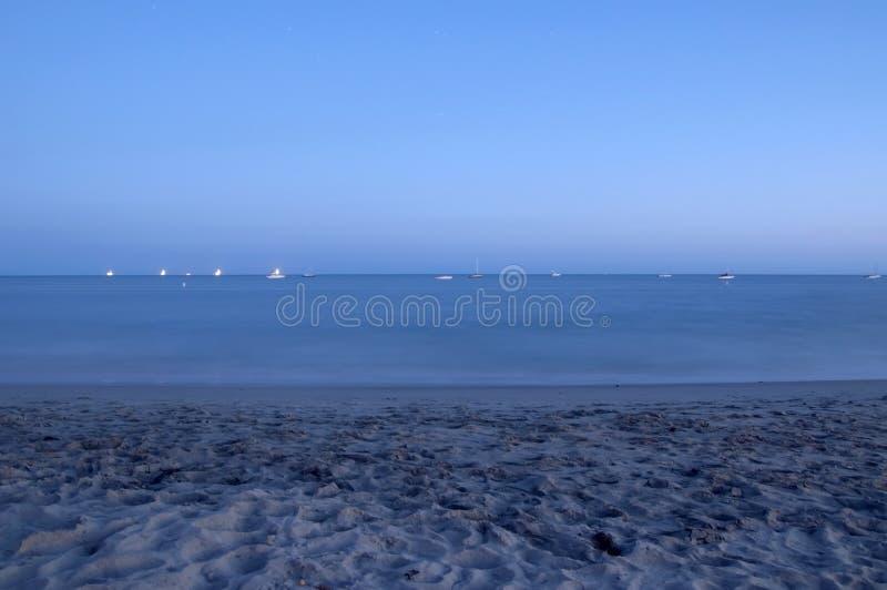 Oceaan en strand bij schemer stock fotografie