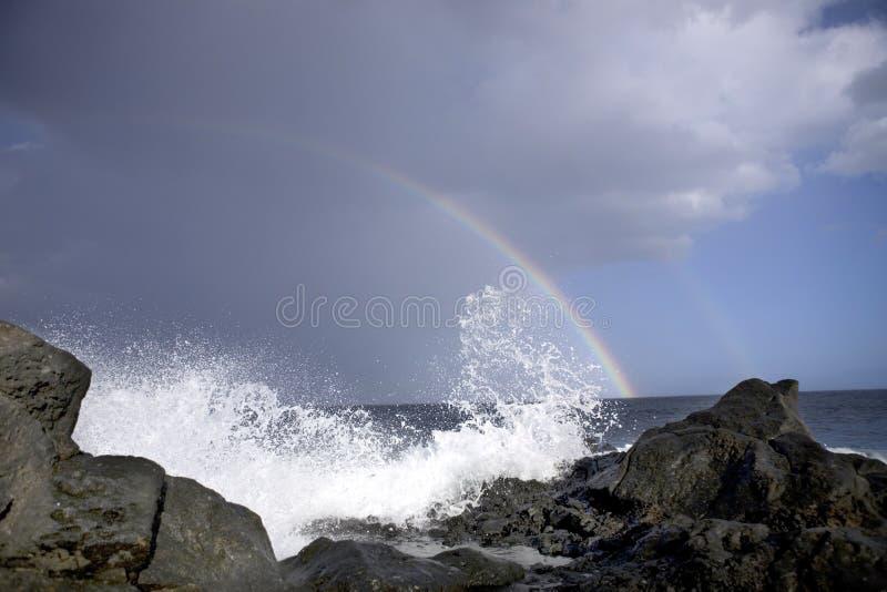 Oceaan golven en regenboog stock afbeeldingen