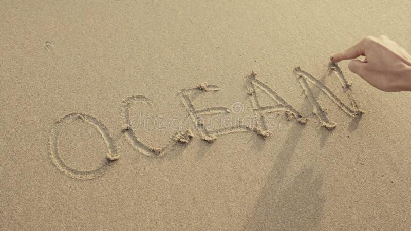 OCEAAN op het strandzand wordt door golven altijd wordt gewassen geschreven die royalty-vrije stock foto