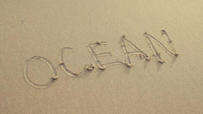 OCEAAN op het strandzand wordt door golven altijd wordt gewassen geschreven die stock afbeeldingen