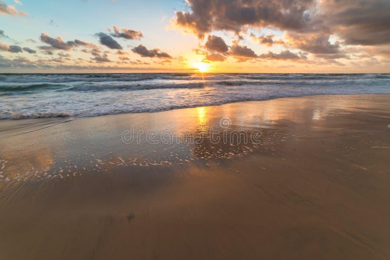 Oceaan zandige kust met zachte golven tegen zonsopganghemel op bac stock afbeeldingen