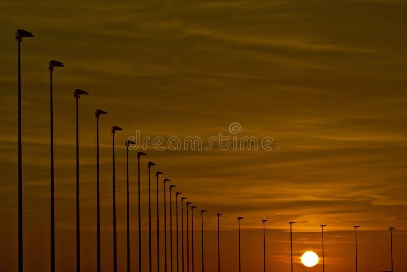 Oceaan zonsondergang en straatlantaarns royalty-vrije stock foto's