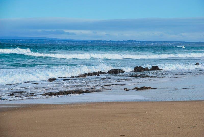 Oceaangolven die aan het zandige strand, inwonersland op de achtergrond rollen Oceaanbosje, Victoria, Australië royalty-vrije stock foto's