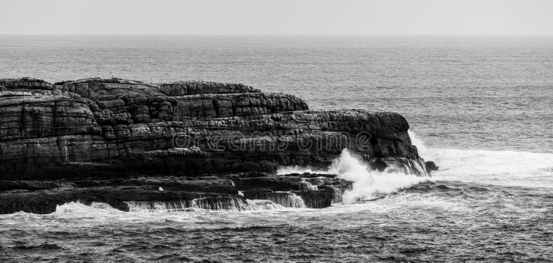 Oceaangolven die op ruwe kustklippen breken Zwart-wit l stock afbeelding