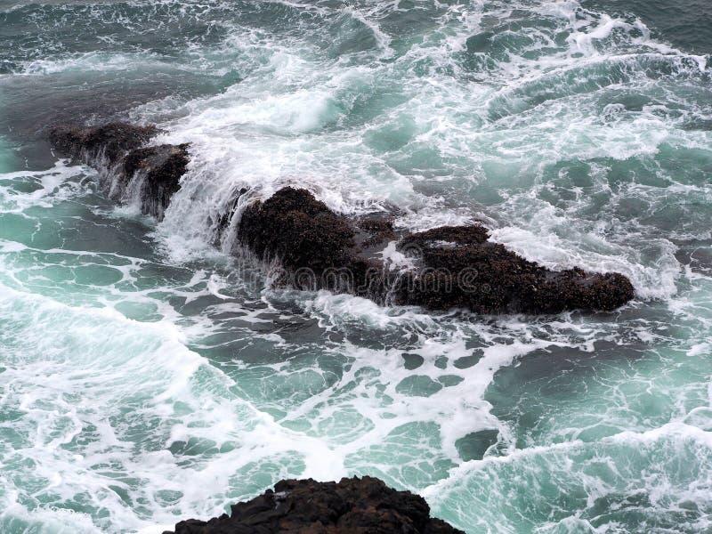 Oceaangolven die over de Ruwe Rotsen van de Vreedzame Kust stromen stock afbeelding