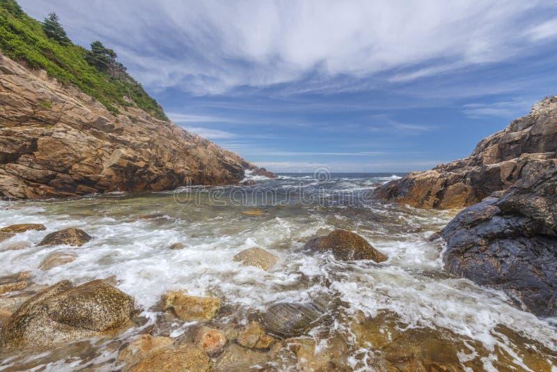 Oceaangolven die tegen een rotsachtige kust verpletteren stock foto's