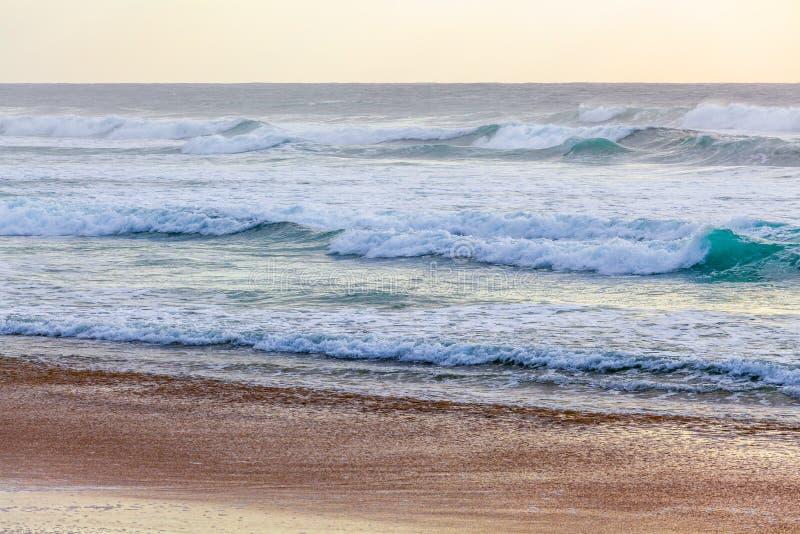 Oceaangolven en strandzand bij zonsondergang stock afbeelding