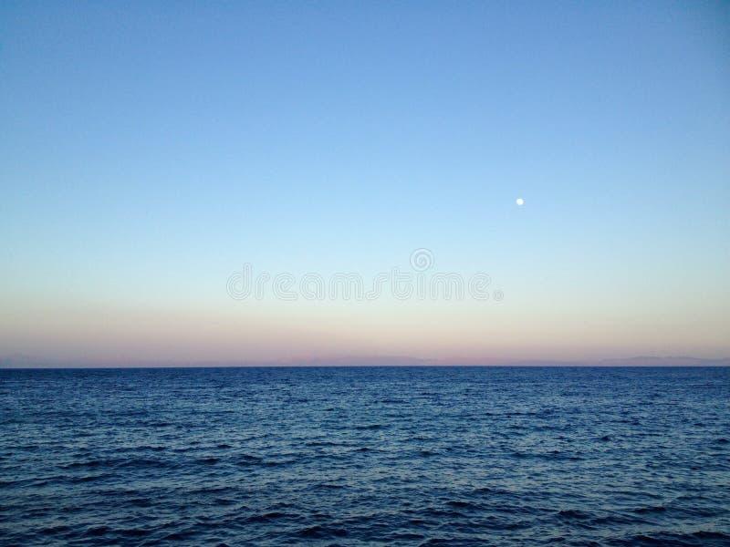 Oceaanhorizon met duidelijke hemel en maan bij zonsondergang royalty-vrije stock afbeelding