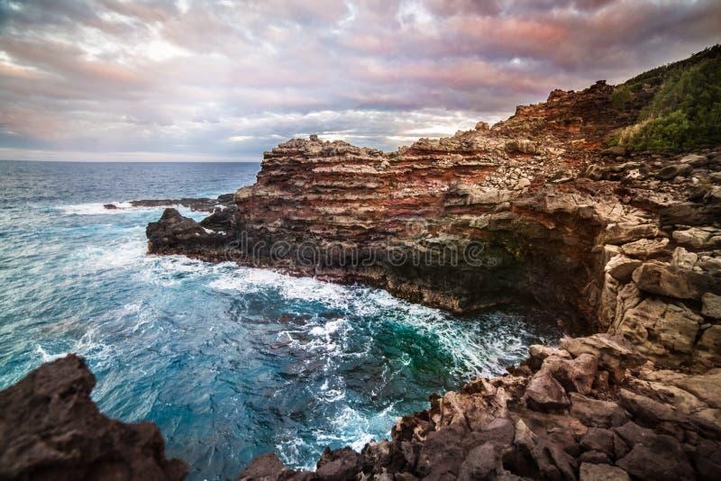 Oceaanklippenbaai met blauw duidelijk water in zonsondergangtijd op het tropische eiland van Maui, Hawaï stock foto's