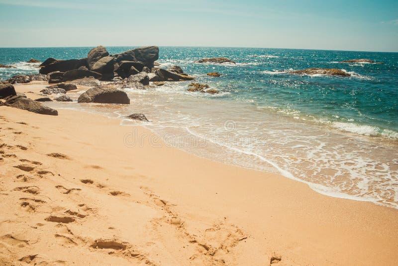 Oceaankust met stenen en sodawateroppervlakte Tropische vakantie, vakantieachtergrond Verlaten voetafdrukkenstrand Paradijsidenti stock afbeeldingen