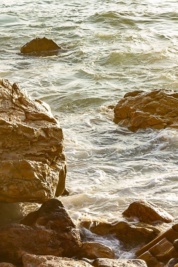Oceaanwater omringende keien en rotsen bij kust, met lichte bezinning royalty-vrije stock fotografie