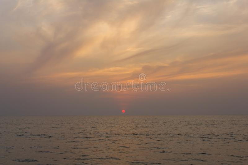 Ocean against a purple sunset sky with bright red sun. A ocean against a purple sunset sky with bright red sun royalty free stock photo