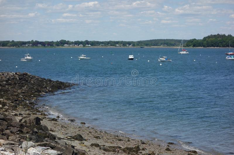 Ocean bay with breakwater, sharp spit of land, boats. Casco Bay, Portland, Maine, in summer with white boats moored in water, rocky point of land stock photo