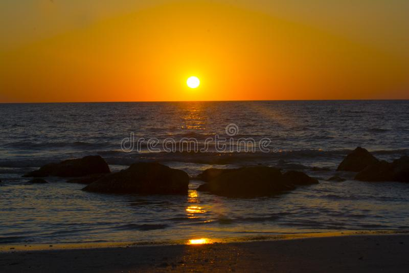 Ocean beach dramatic sunsets. Orange skies and blue waters of the florida Gulf of Mexico as the sunsets. Waves rolling in royalty free stock photos