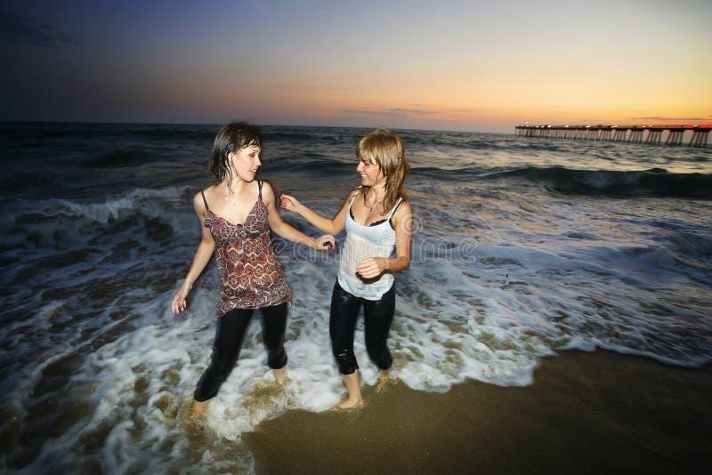 Ocean beach fun. Two girls having fun at ocean beach at sunset stock photos