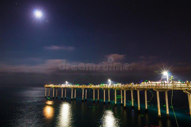 Ocean beach night view with fisherman stock photos