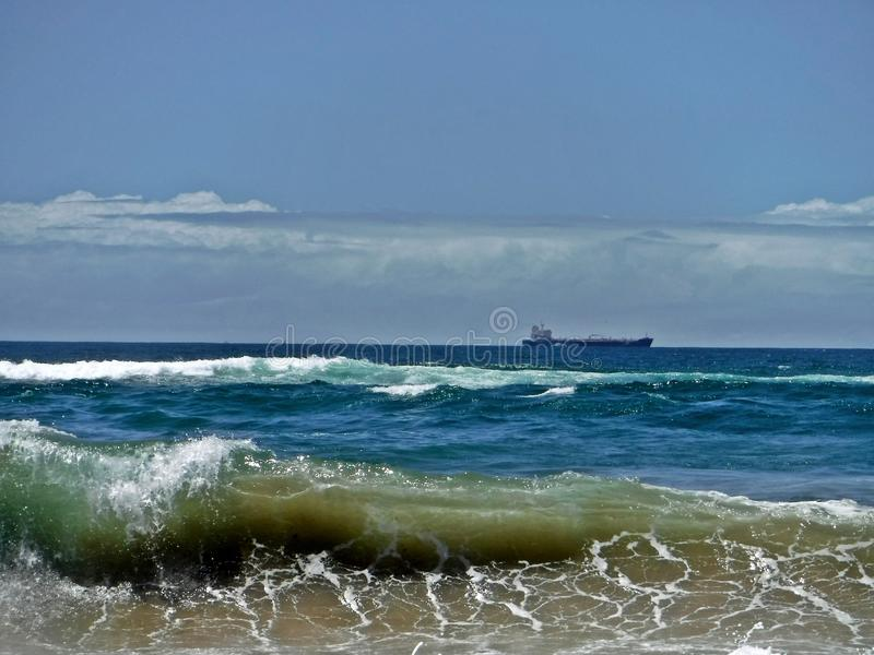 Ocean and beyond. Waves break at a beach north of Durban with merchant ship in background royalty free stock image