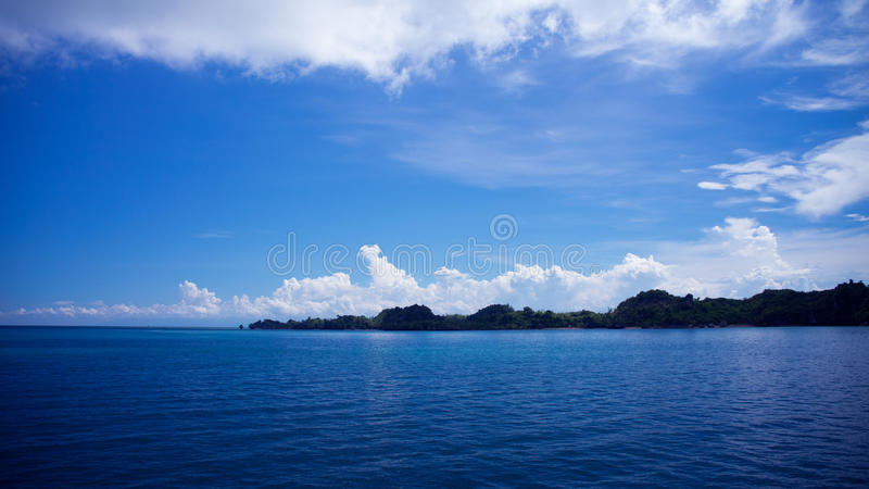 The ocean with bright blue skies and white clouds. Landscape view of the ocean with bright blue skies, white clouds, and an island. This image can be used as a stock image