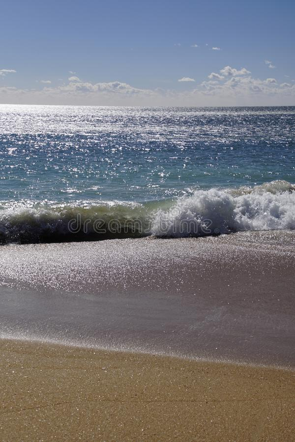 Ocean coast. Beautiful waves of the surf in the rays of the sun. Sandy beach r stock photography