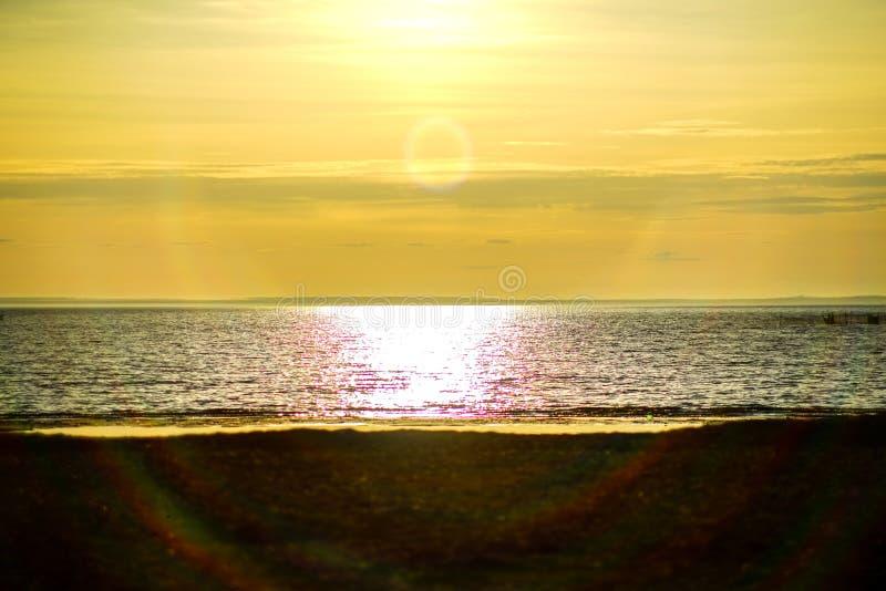 Ocean, denny zmierzch na tle słońce iść poza horyzont plaża i cudowny zdjęcie royalty free