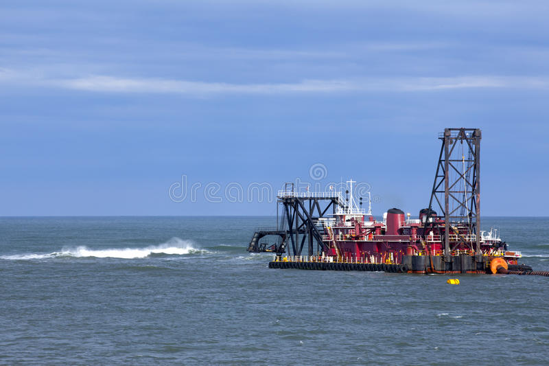 Ocean Dredge. Working on a shallow part of an inlet and pumping sand to a beach as part of a replenishment project royalty free stock image