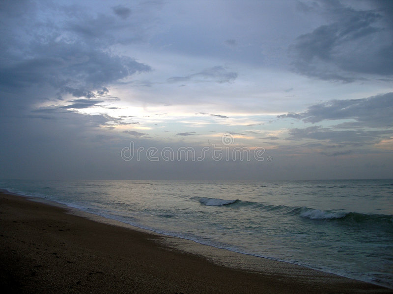 The Ocean at Dusk. The lasts strands of light fade away as the sun sets on the other side royalty free stock photography